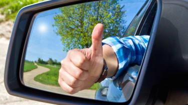 Car driver ith thumb up in a side mirror