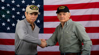 photo of two veterans shaking hands in front of American flag
