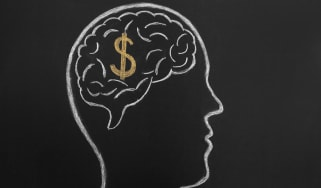 A chalkboard drawing of a man's brain with a dollar sign in it.