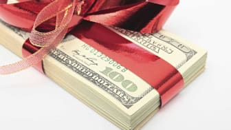 picture of a stack of money with a red bow tied around it