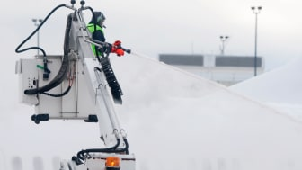 airplane being sprayed with deice fluid during a snow storm