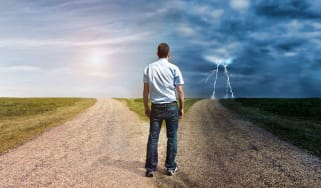 Man standing in fork in the road between good and bad weather