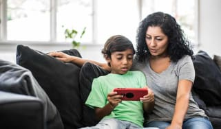 Mother and son looking at device at home