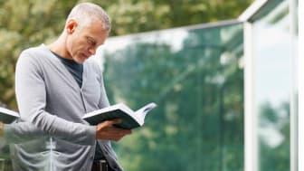 Senior man reading book on balcony