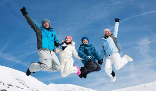 picture of happy family in the snow jumping into the air