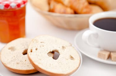 Doughnut cut in half and a cup of coffee on white plates with sugar and milk and a pot of jam