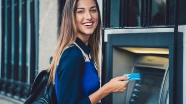 Young woman at ATM outside of bank