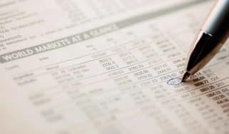 A pen marking an item in a newspaper stock chart.