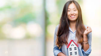 picture of happy woman holding a model house