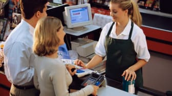 A supermarket clerk helps a couple check out there groceries
