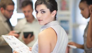 A successful woman at work looks over her shoulder.