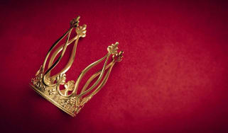 A gold crown against a red background