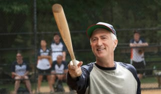 A retiree smiles as he warms up his softball swing.
