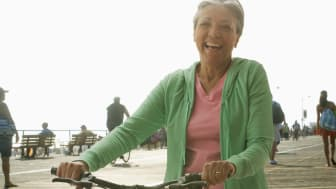Smiling senior next to her bike on a New Jersey boardwalk