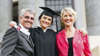 picture of parents with daughter in college graduation cap and gown