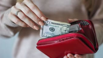 A woman pulls cash from a wallet