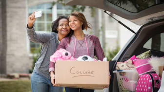 picture of mother and college student daughter taking selfie while moving into dorm