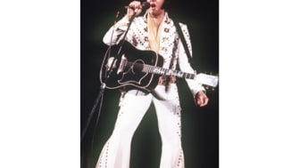 """**FILE**Elvis Presley sings during a 1973 concert.His music lives on and continues to set records in Britain.On Sunday, Jan. 16 2005, """"One Night""""tookthe number one position on the country's s"""