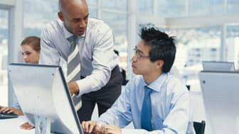 Businessman pointing at computer monitor and explaining to man