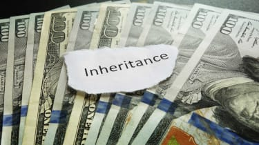 """picture of a piece of paper with """"inheritance"""" written on it laying of fanned out one-hundred dollar bills"""