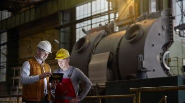 Male engineer and worker using digital tablet in dark factory