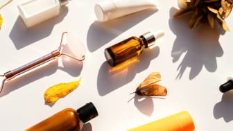 Autumn concept with beauty cosmetics products and fall leaves. Skin care beauty products, natural cosmetic. Natural cosmetic skincare bottle, serum, oil, cream, rose quartz facial roller.