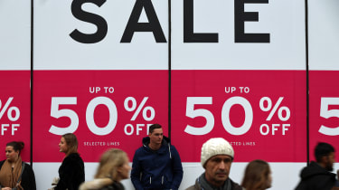 LONDON, ENGLAND - DECEMBER 30: People walk past a sale sign outside a department store on Oxford Street on December 30, 2015 in London, England. Shoppers are continuing to spend as stores off