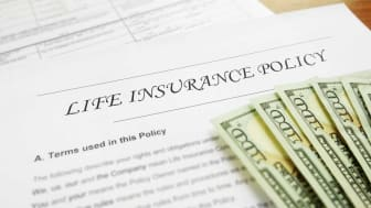 picture of a life insurance contract with money laying on it