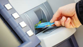 Niort, France - March 27, 2017 : closeup of young woman welldressed with beautiful hands and pretty manicured nails inserting her bank card in a distributor of banknotes usually called ATM ca