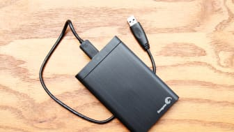 """""""West Palm Beach, USA - September 6, 2012: Product shot of a Seagate portable one terabyte external hard drive with attached cable.Editorial studio product shot on a wood desk background."""""""