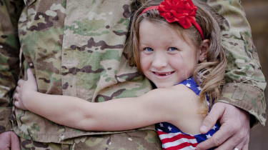 Child hugging a military service member.