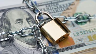 Closeup of metallic chain and padlock around dollar bundle