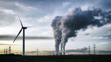 A windmill near some smoke stacks