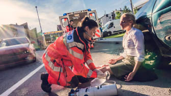 An EMT helps an injured woman at the scene of an accident