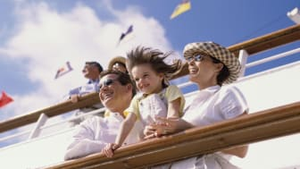 Low angle view of parents with their daughter standing on the deck of a cruise ship