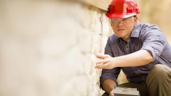 Repairman, building inspector, exterminator, engineer, insurance adjuster, or other blue collar worker examines a building/home exterior wall.He wears a red hard hat and clear safety glasses