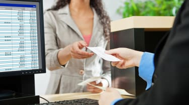 Over-the-shoulder shot of a transaction between a bank teller and a customer in a retail bank. The teller is wearing a black suit and receiving a check from the tan-suited customer over the b