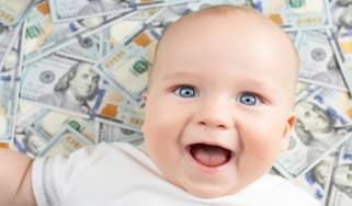 picture of smiling baby laying on one-hundred dollar bills