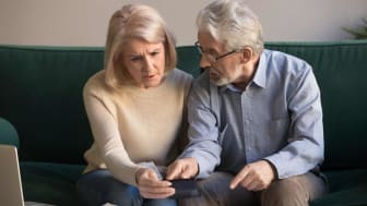 Seriously stressed older couple looking at calculator feeling worried