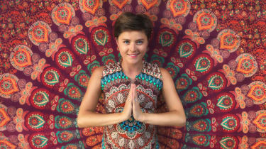 A woman presses her palms together in the namaste yoga pose.