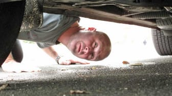 Man checking underbody of car