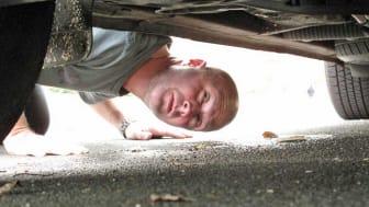 Man checking underbody of car