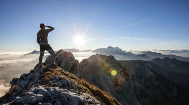 A man climbs to the top of a mountain.