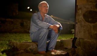 Older man sitting in the backyard at night in his pajamas