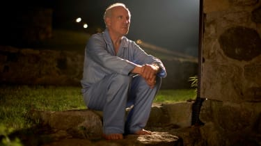 Older man sitting in the backyard at night in his pajamas