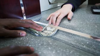 picture of person receiving cash from a bank teller