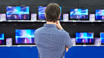 A man looks at rows of televisions in a store's electronics section