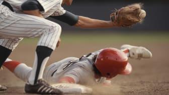 Base runner sliding into base, fielder catching ball in baseball game