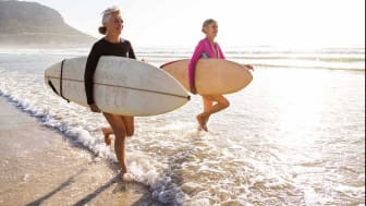 Two women walking in the ocean with their surf boards.