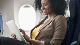 woman smiling while seated on plane